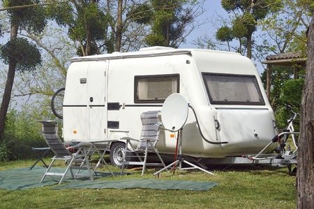 arm chairs: White caravan with arm chairs and satellite dish at the camping