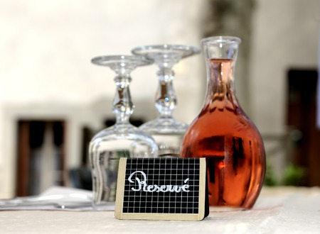 reserved sign: Reserved sign at a restaurant table in France With glasses and a decanter filled with rose wine