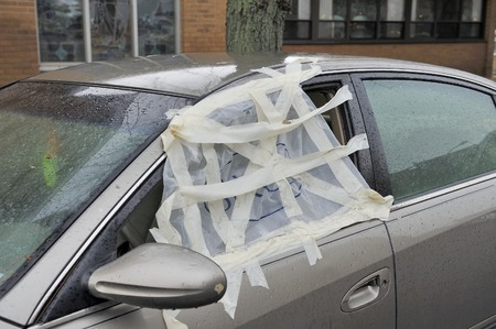 repaired: Smashed car window and temporary repaired with a plastic hide Stock Photo