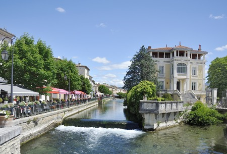 View at Isle-sur-la-Sorgue with the river Sorgue and some restaurants Sorgue river running trough town of L Editorial
