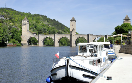 middle ages boat: The XIV century pont Valentre in Cahors in Quercy, Dordogne At foreground two  boats