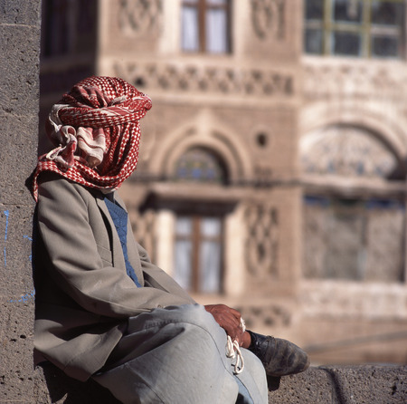 agal: Arab man, seen from the back, with veil. At background typical Yemen house in Sanaa the capital of yemen. Stock Photo