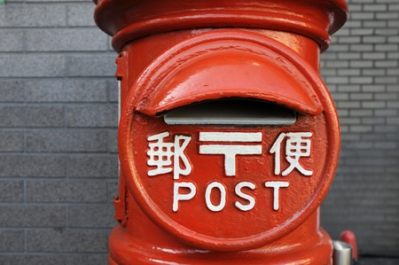Kyoto, Japan-November 11,2014; Japanese red mailbox in close up.With text in japanese characters and English language. Novembver 11, 2014 Kyoto,Japan