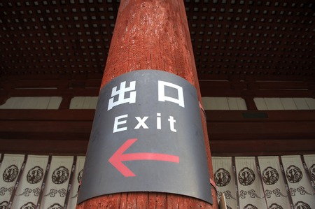 english language: Exit sign with arrow and in Japanese and English language indicating the spot where the exit is situated