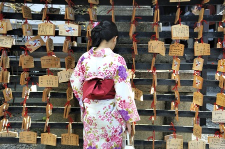ema: Kyoto, japan-November 4, 2014; Geisha in front of prayer tablets at Rokuharamitsuji Temple. People write their wish on a wooden tablet (ema) and leave that at the temple in desire that their wish will come true.Most of the wishes are about love, health, s