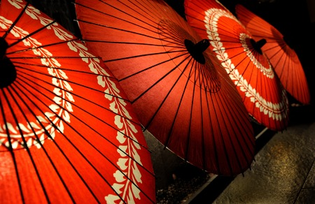 Japanese traditional red umbrellas with with floral motives Stockfoto