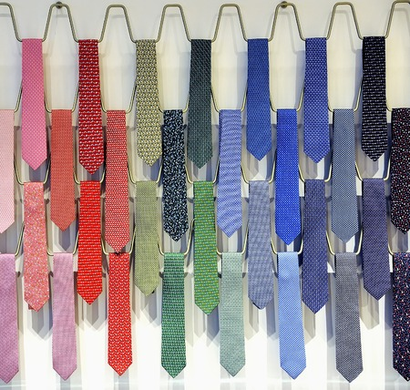 formal dressing: Rows of varicolored silk male business ties on a tie rack