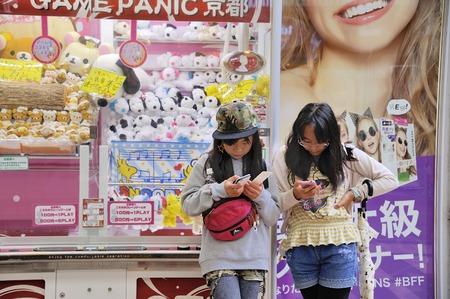 mobiele telefoons: Kyoto, Japan-9 november 2014; Twee meisjes kijken naar hun mobiele telefoon in een winkelcentrum center.November 9, 2014 Kyoto, Japan Redactioneel
