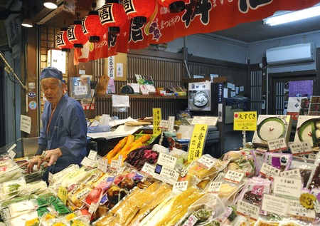 Kyoto, Japan - November 9, 2014: Fish vendor at food market stall in Nishiki market in Kyoto. Nishiki Market is famous in the city for high quality and gourmet foods. November 9, 2014 Kyoto, Japan