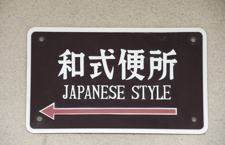 defecate: Sign in Japanese characters and English language to bathroom in Japanese style Stock Photo