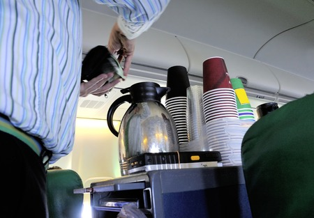 Steward pouring coffee in the cabin of an airplane