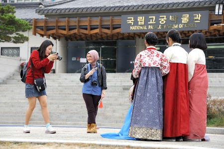 korea girl: Seoul, South Korea-November 10, 2015; Girl taking pictures of friends in traditional costume. In front of the National Palace Museum of Korea. November 10, 2015 Seoul, South Korea