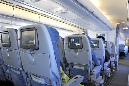 persona viajando: Los pasajeros sentados en asientos de clase turista en el interior de un avión Editorial