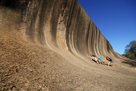 HYDEN,AUSTRALIA-FEBRUARY 13, 2015; Wave Rock, with three young tourists, near Hyden in Western Australia. February 13, 2015 Hyden, Australia Editorial
