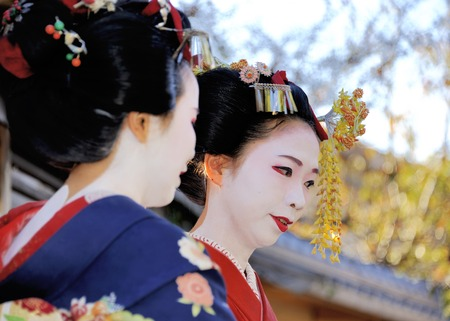 culturally: KYOTO,JAPAN - NOVEMBER 4, 2014: Geisha women in traditional dress. Kyoto is center of Japans traditional culture. Kyoto has 17 Unesco World Heritage Sites and is one of the worlds most culturally rich cities and is the capital of the geisha world. They