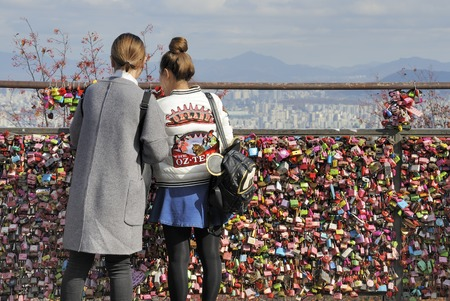 Seoul, South Korea - November 12, 2015: Two women looking at thousands of love padlocks at Namsan Seoul Tower. Locks of love is a custom in some cultures which symbolize their love will be locked forever. November 12, 2015 Seoul South Korea