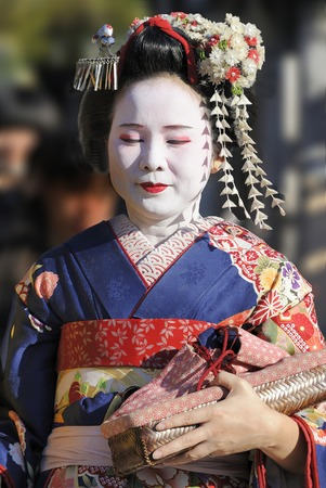 culturally: KYOTO, JAPAN - NOVEMBER 4, 2014: Geisha woman in traditional dress. Kyoto is center of Japans traditional culture. Kyoto has 17 Unesco World Heritage Sites and is one of the worlds most culturally rich cities and is the capital of the geisha world. They Editorial