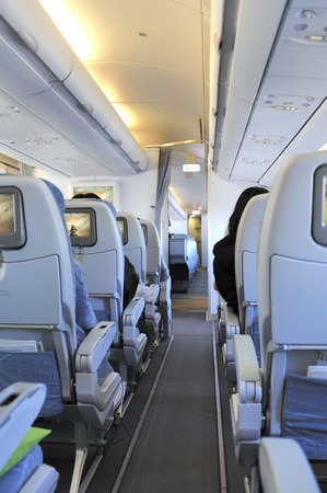 carves: Passengers in the tourist class sitting in their seats of the airplane