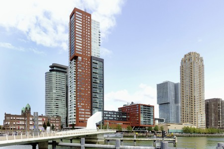 ROTTERDAM, HOLLAND-AUGUST 30, 2018. New York City, Montevideo tower and world Port at Kop van Zuid, a relatively new area on the south bank of the river which is well known for its iconic architecture. The Rijnhavenbridge on foreground without people.