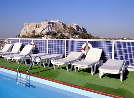 ATHENS, GREECE-MAY 12, 2015: Acropolis in Athens; in front swimming pool at hotel roof. The Acroplois site is an UNESCO World Heritage landmark.