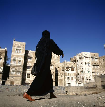 A veiled Muslim woman walks on a Sanaa street, Yemen.At background typical Yemen houses.