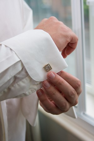 Groom preparing for his wedding day checking his cuff links. photo