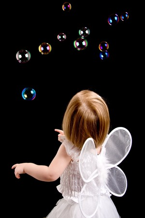 Little girl dressed as an angel with bubbles in the background. photo