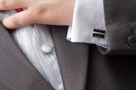 cuff link: cuff link on groom whilst preparing for his wedding,