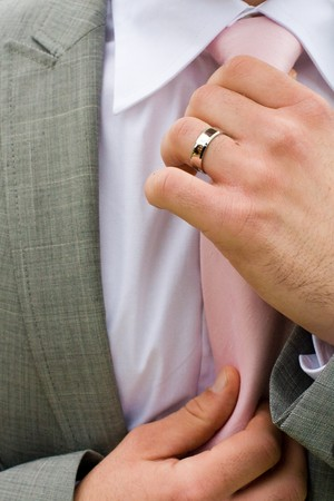cufflink: Ascertive man checking his tie with a business suit.