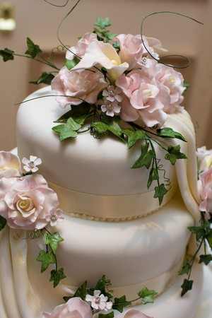 Wedding cake with pink roses and green foliage icing. Stock Photo