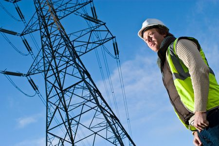 pylon: Man in front of an electricity pylon Stock Photo