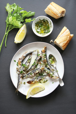 a portion: Grilled sardine with salsa verde on a plate.Top view