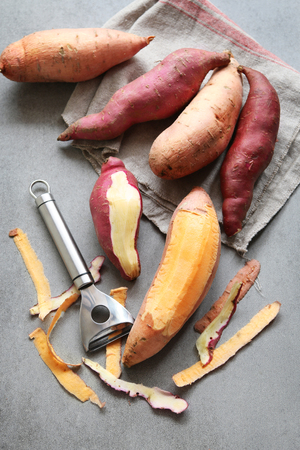 sweet foods: Two varieties of sweet potatoes on grey background