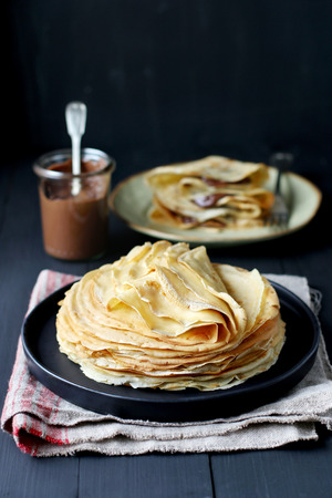pancake: Stack of crepes on a plate with a jar of chocolate spread on background