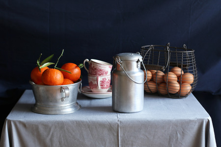 clementine fruit: Still life with clementines,aluminum milk can,eggs and vintage coffee cups
