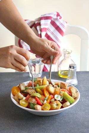 aceite de cocina: Mujeres de mezcla los ingredientes para la ensalada panzanella Foto de archivo