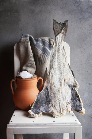sal: Salted cod fish and a rustic clay pot with sea salt  on a white chair