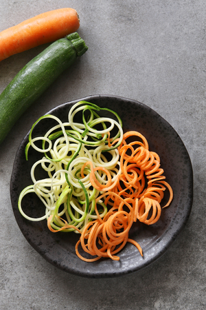 vegetable squash: Spiral zucchini and carrot spaghetti imitation noodles on a plate.Top view. Stock Photo
