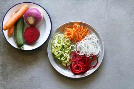 rutabaga: Spiral zucchini,carrot,turnip and beetroot spaghetti imitation noodles on a plate.Top view.
