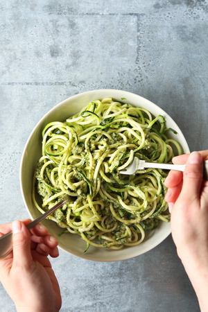 Female hands mixing zucchini noodles with pesto sauce.Top view Stock Photo