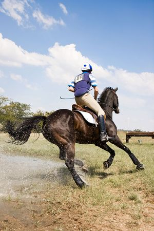 Horse and rider turning for the next fence, after successfully negotiating a water jump, in a cross country event. Stock Photo