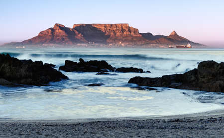The mid winter sunrise lights up the front of Table Mountain as viewed from Bloubergstrand in Cape Town, South Africa.