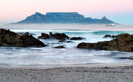 Long exposure of Table Mountain at twilight as viewed from Bloubergstrand beach in Cape Town, South Africa. Stock Photo