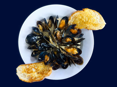 A dish of appetizing fresh mussels in white wine sauce served with toasted bread.