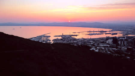 Aerial, drone view of sunrise over Table Bay and Cape Town Harbor in  South Africa. Stock Photo