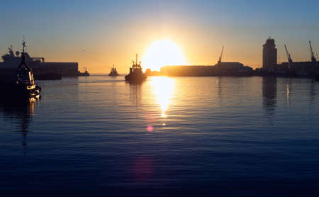 Tugboats silhouetted against the sun as they leave harbor.