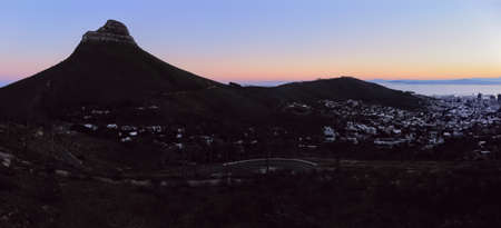 Aerial drone panoramic of Lion's Head and Signal Hill silhouetted against the twilight sky in Cape Town, South Africa.