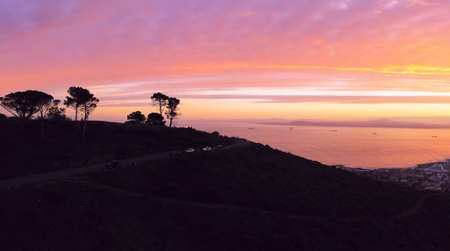 Aerial, drone panoramic of the top of Signal Hill silhouetted against the dawn sky and Table Bay in Cape Town, South Africa. Stock Photo