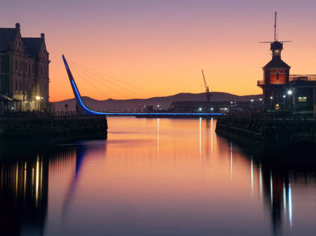 Dawn view of a harbor entrance and its pedestrian swing bridge edged with blue neon strip lights. Stock Photo