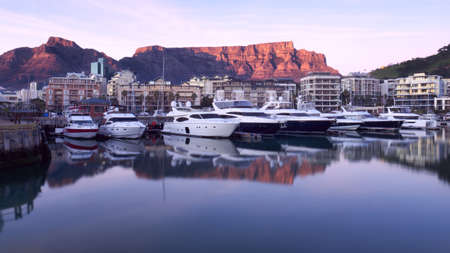 Table Mountain sunrise is reflected in the still waters of a marina for luxury motor yachts in Cape Town, South Africa. Stock Photo